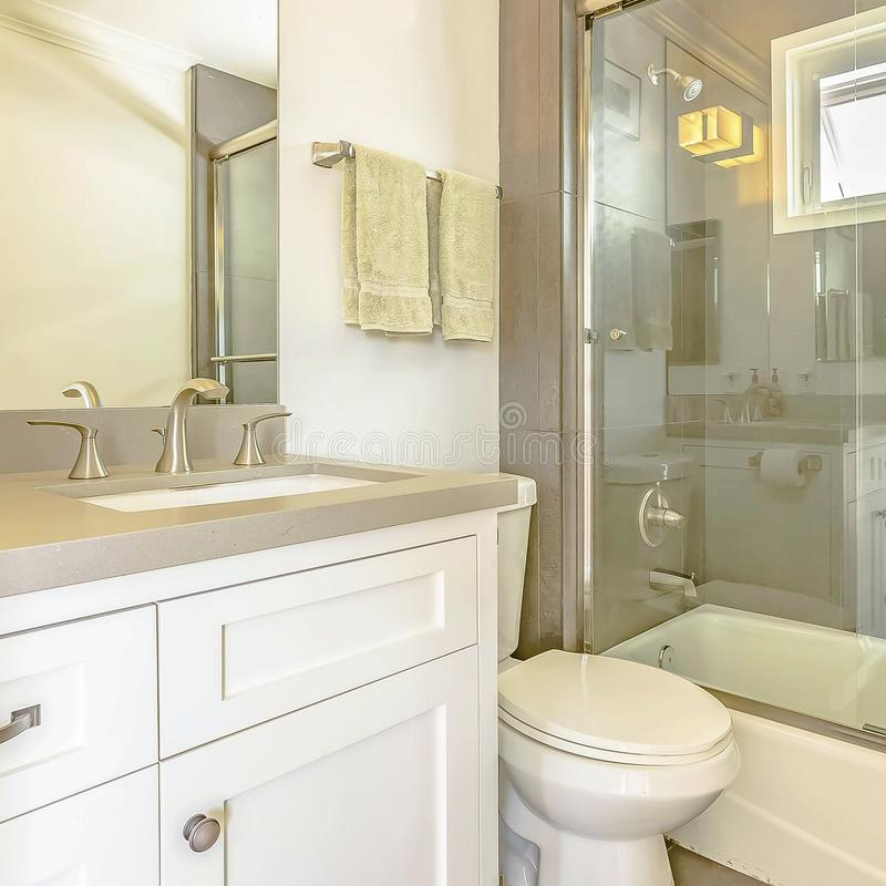 Frame Square Bathtub and shower with glass door and window inside the bathroom of a home. The toilet and vanity unit can also be seen in this small room royalty free stock photography