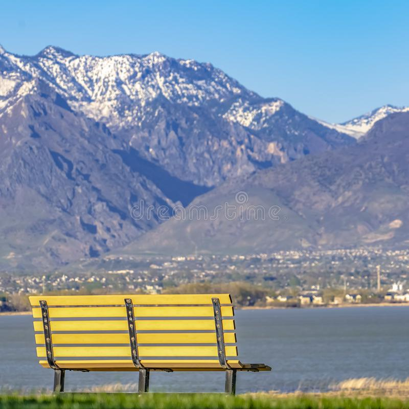 Frame Square Empty bench facing an amazing view of a lake and mountain capped with snow royalty free stock image