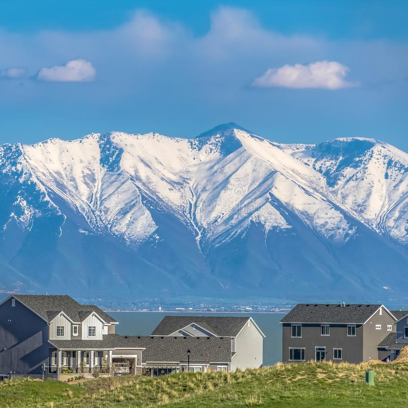 Frame Frame Square Grassy hill with houses overlooking a vast lake and snow capped mountain. Cloudy blue sky cna be seen over the valley on this sunny day stock images