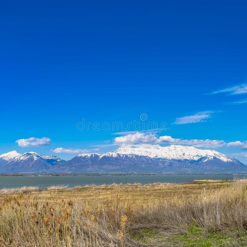 Frame Square Panorama of a mountain with snowy peak towering over a lake with grassy shore stock photo