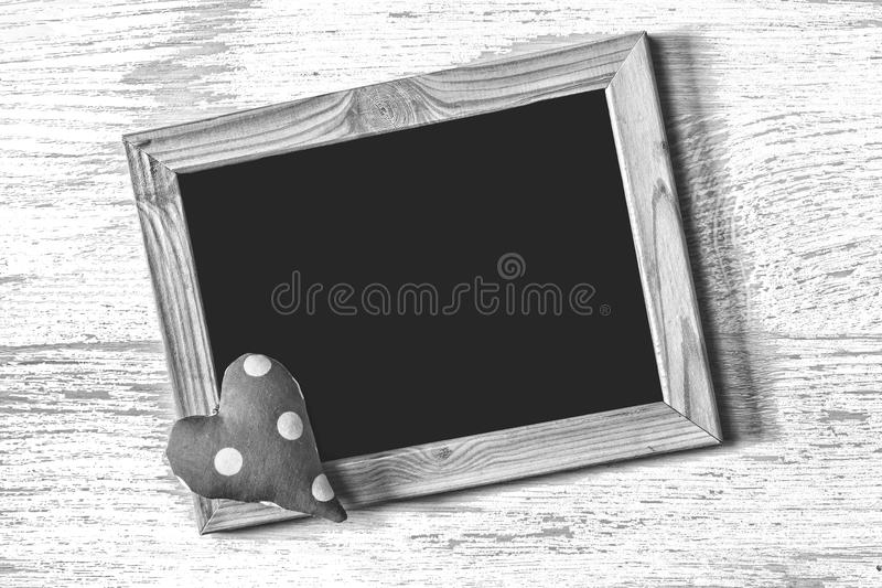 Frame of St. Valentine`s Day and homemade heart on a white wood texture board. Close up stock photography