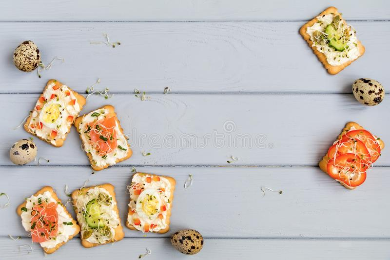 Crackers with cream cheese and various toppings. Appetizers on grey table. Healthy snacks, top view, flat lay. Frame of tasty crackers with cream cheese, sweet royalty free stock image