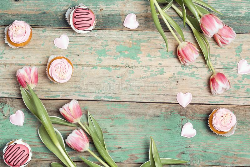 Frame of tasty cupcakes with tulips on vintage wooden table. Romantic love background. Copy space, overhead shot stock photo