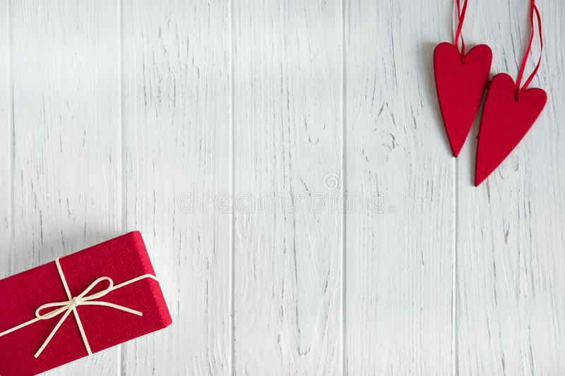 Frame for text greeting card for Valentine`s day. Box with a gift and red hearts on a light wooden background. Frame for royalty free stock photos