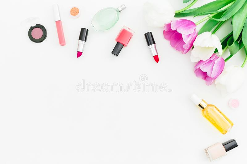 Frame with tulips flowers and cosmetics with perfume on white background. Top view. Flat lay. Copy space stock photos