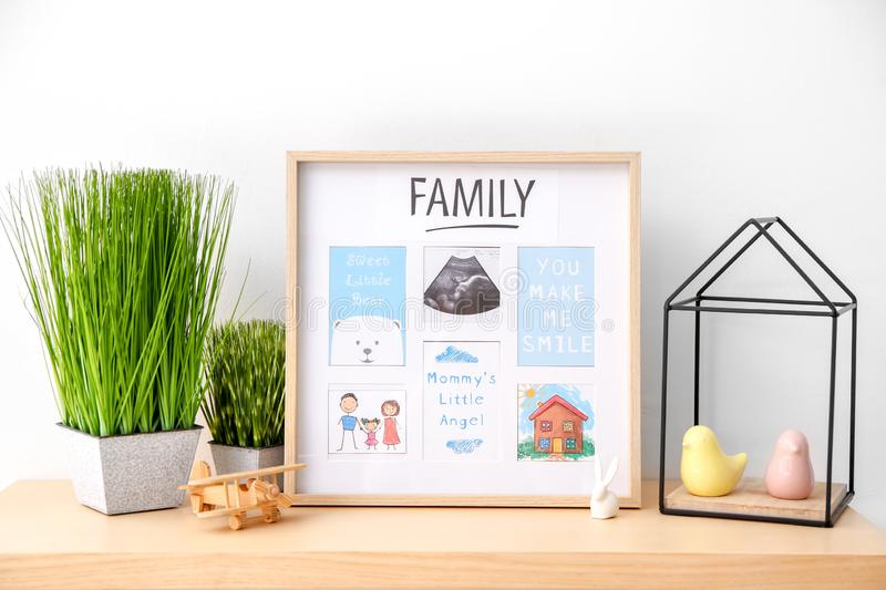 Frame with ultrasound photo and sweet words from mother to baby on table stock photo
