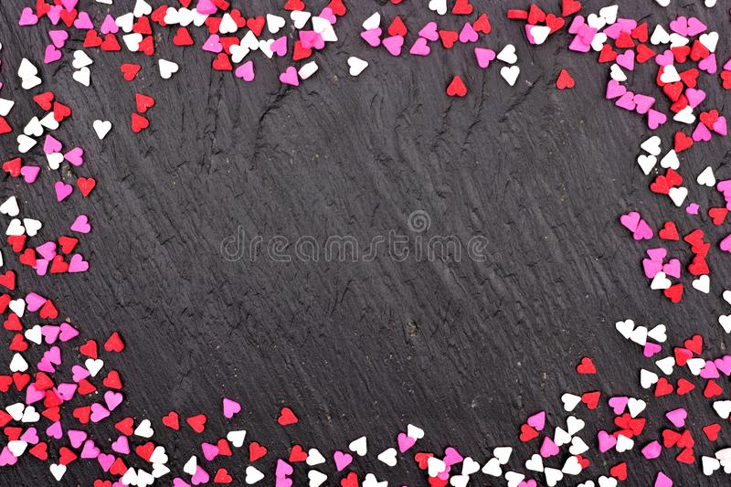 Valentines Day candy heart sprinkles frame over a black background stock photos