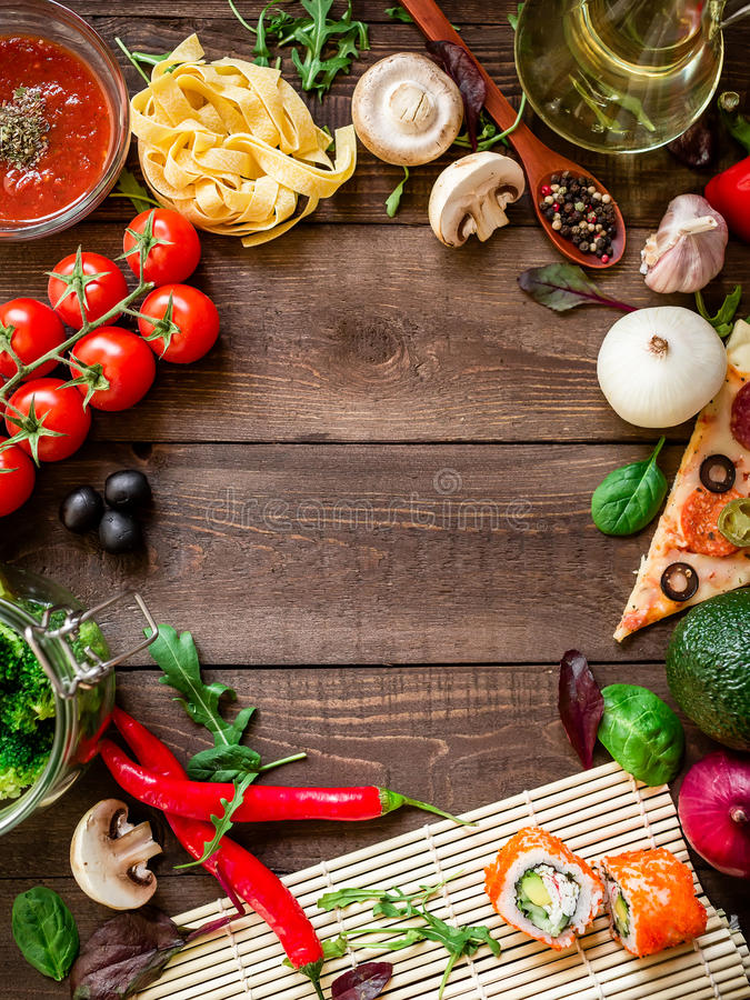 Frame with vegetables, pizza, sushi rolls, tomato, pasta, olives and sauce on wooden background. Food concept for menu. Flat lay. stock images