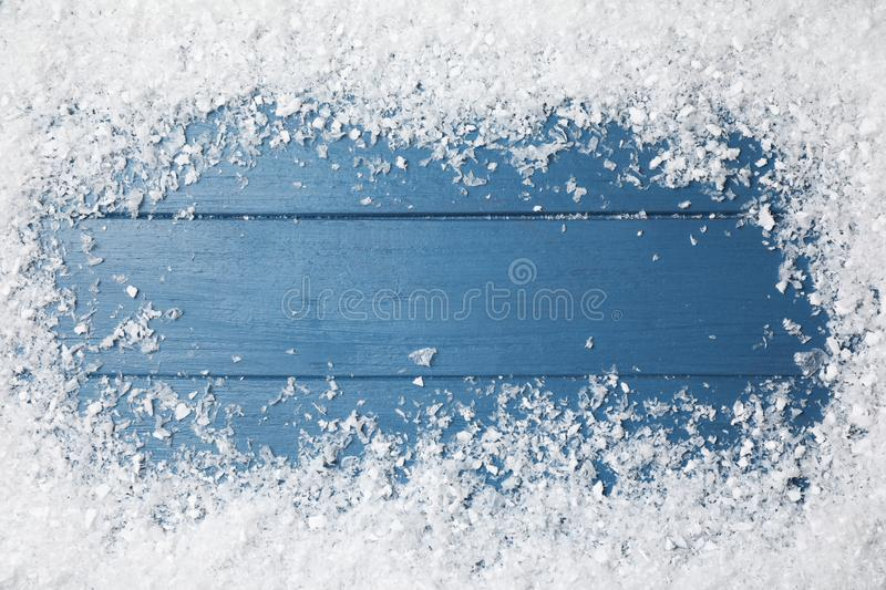 Frame of white snow on blue wooden background, top view. Christmas season. Frame of white snow on blue wooden background, top view with space for text. Christmas stock photography