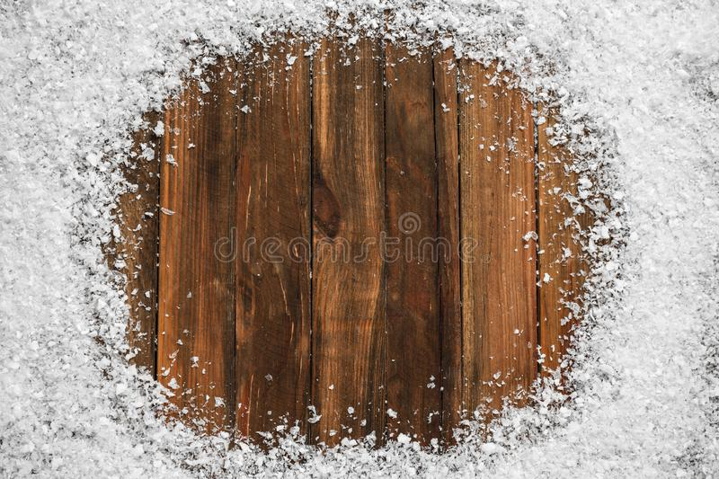 Frame of white snow on wooden , top view with space for text. Christmas season. Frame of white snow on wooden background, top view with space for text. Christmas royalty free stock photo