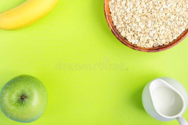 Frame from Wooden Bowl with Rolled Oates Jug with Milk Banana Green Apple on Pistachio Background. Balanced Healthy Diet Fiber stock photos