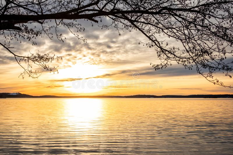 Framed beautiful orange winter landscape sunset over calm lake water with bright sun against sea horizon. royalty free stock photography