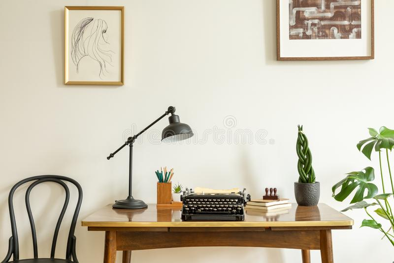 Framed drawing on a white wall above an antique, wooden desk with a vintage, black typewriter in a home office interior stock image