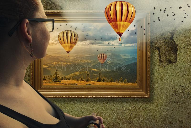 Framed illusion. Young woman looking at classic baroque picture frame on grunge, textured wall with landscape showing hot air balloons from another world
