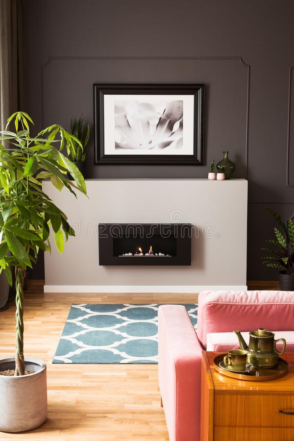 Framed photo above a minimalist, modern fireplace in a stylish living room interior with vibrant stock photography
