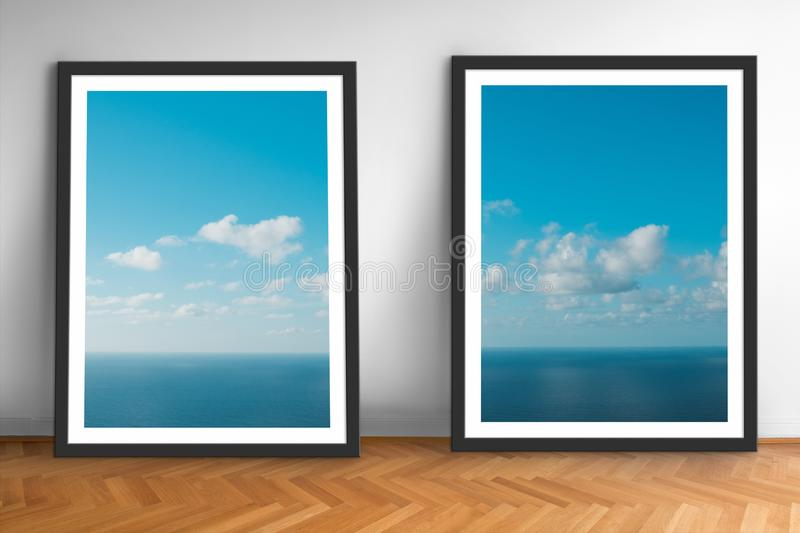 Framed picture prints of ocean and blue sky landscape photography on wooden floor royalty free stock images
