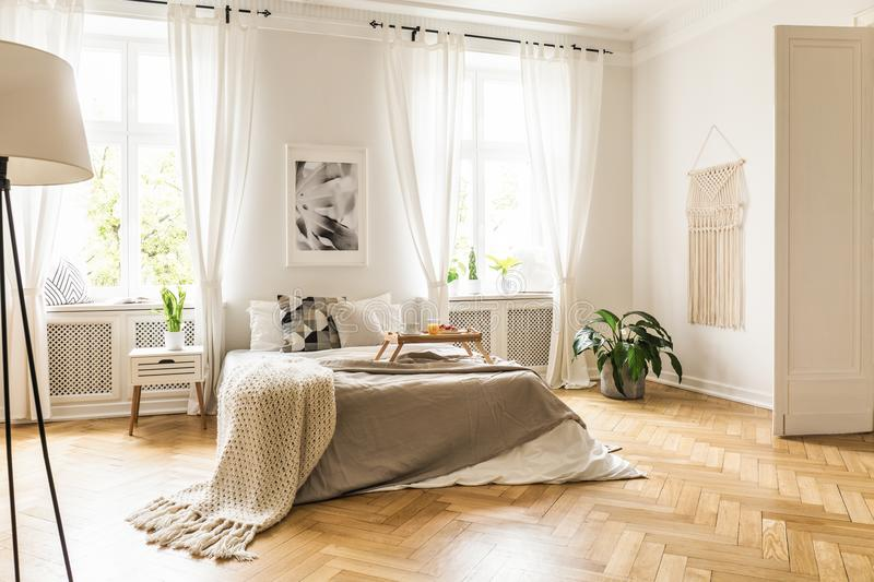 Framed poster on a white wall above a cozy double bed with beige. Sheets and breakfast tray in a spacious, sunny bedroom interior stock photography