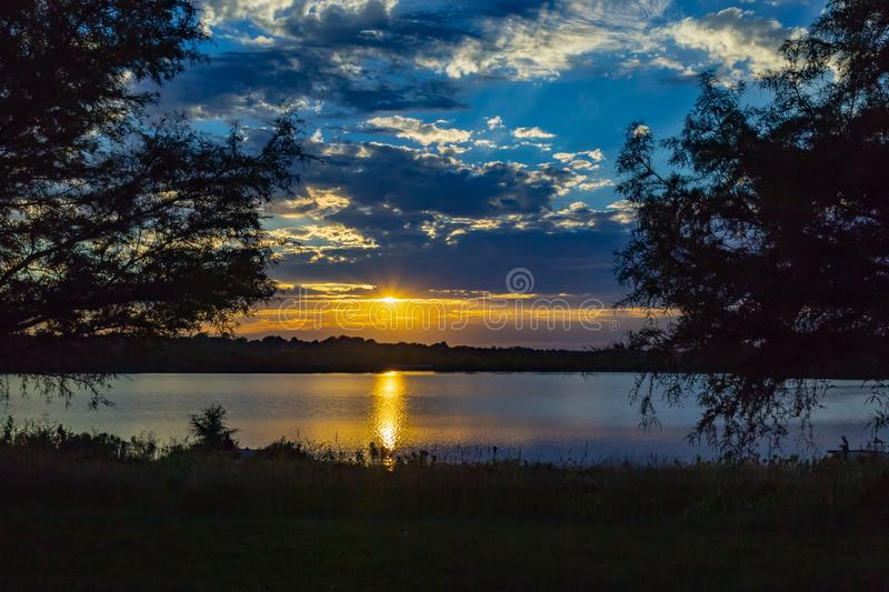 Framed Sunset with beautiful skyline over lake Zorinsky Omaha Nebraska. Framed Sunset with beautiful clouds in the sky and lake with golden sun reflection on the stock photos