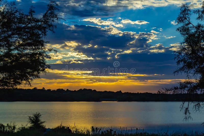 Sunset with beautiful skyline over lake Zorinsky Omaha Nebraska. Framed Sunset with beautiful clouds in the sky and lake with golden sun reflection royalty free stock photography