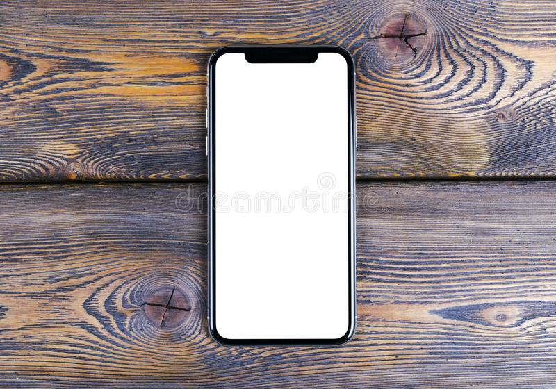Frameless mockup smartphone with blank screen and modern frame less design on office desk. Isolated white screen. Copy space. Empt royalty free stock image