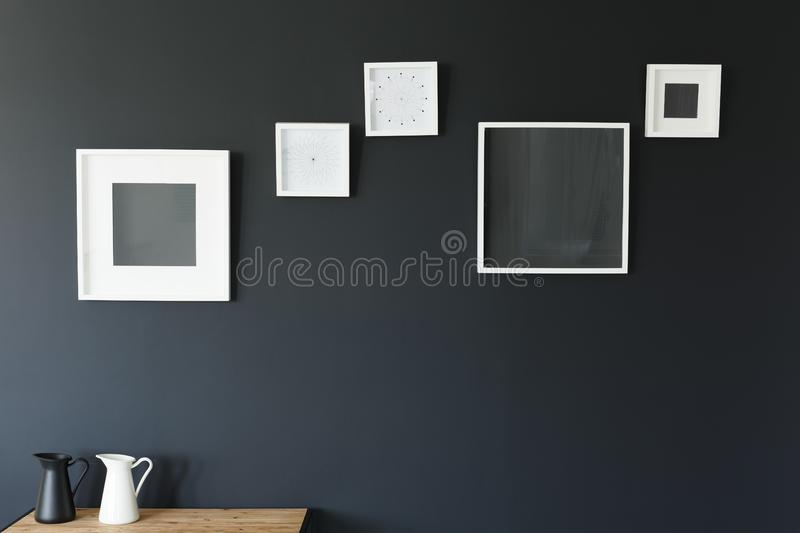 Frames and jugs on table. White mockup frames and black and white jugs on wooden table stock image