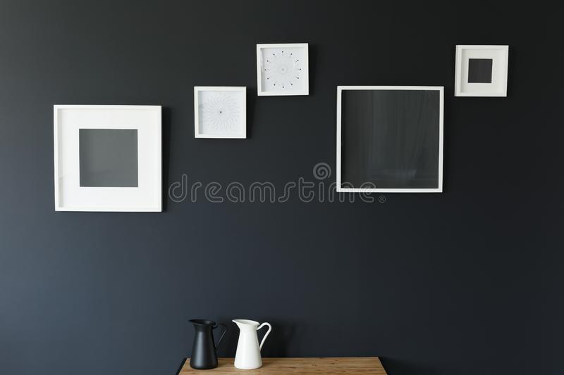 Frames, table, and jugs. White mockup frames, wooden table, and black and white jugs royalty free stock image