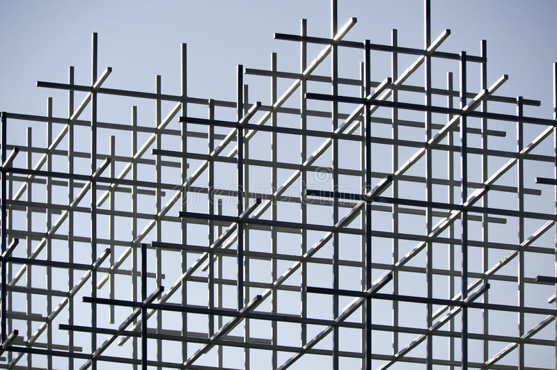 Framework. A metal framework of squares seen from below against a blue sky royalty free stock photo