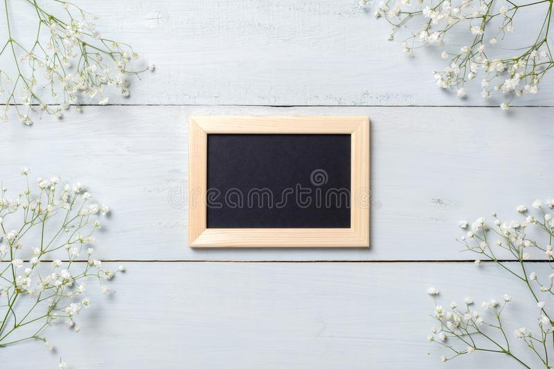 Framework for photo or congratulation on blue rustic wooden desk with flowers. Spring background, banner mockup for Womens or Moth. Ers Day, Easter, spring royalty free stock photos