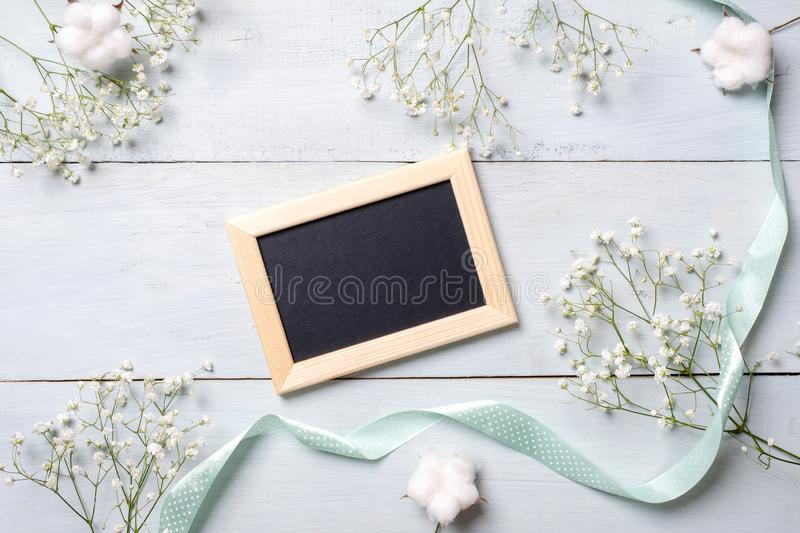 Framework for photo or congratulation on blue wooden background. Banner mockup for womans or mothers day, easter. Spring holidays royalty free stock image