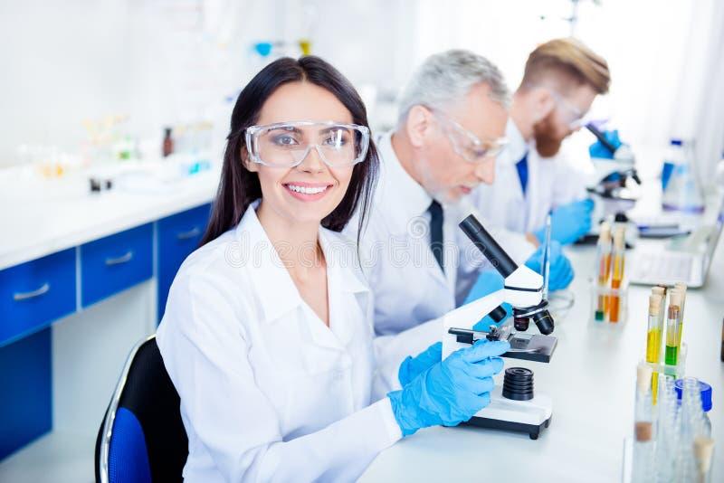 Framgång, i uppfinning av ny teknik! Den unga labbarbetaren ler arkivbild