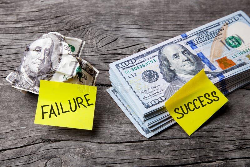 Framgång och fel i affären, val av vägar, begrepp Kontorsklistermärkear på bucklig sedel och högen av dollar royaltyfri bild