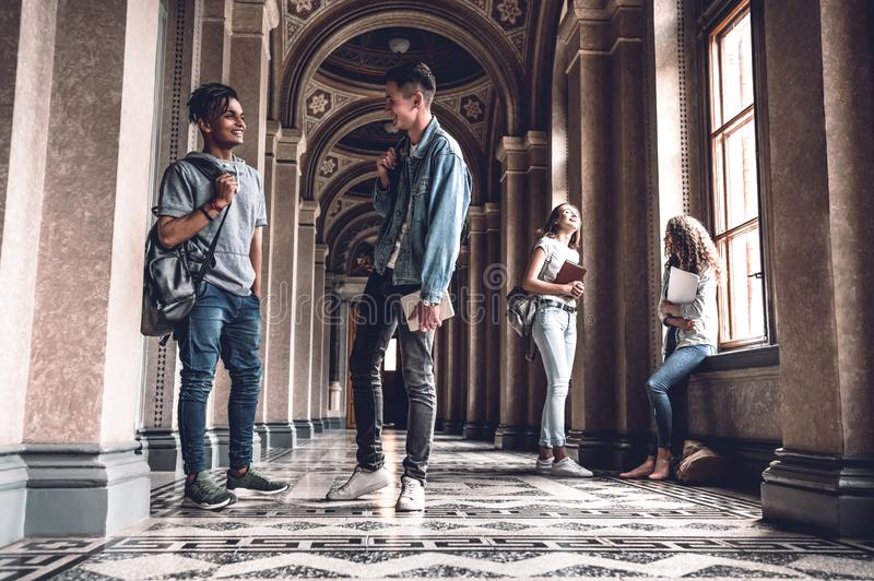 Framgång och kunskap hjälper oss på examen Lyckliga unga studenter som står på korridoren och prata för universitet royaltyfri foto