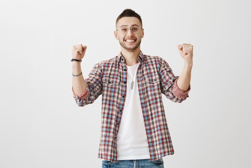 framgång- och segerbegrepp Känslobetonad ung caucasian man med borstet, bärande plädskjorta över t-skjortan och stilfullt royaltyfria bilder