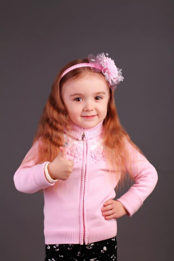 Framgång tummar upp tecken Hon har ett stort lyckligt leende royaltyfri bild