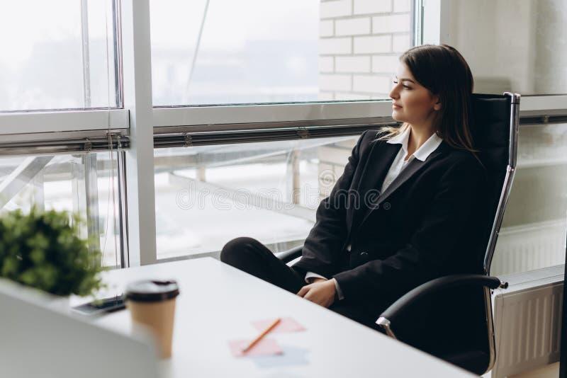 Framgångbefruktning Stående av ursnyggt ungt businesslady sammanträde på hennes arbetsplats i kontoret arkivfoto
