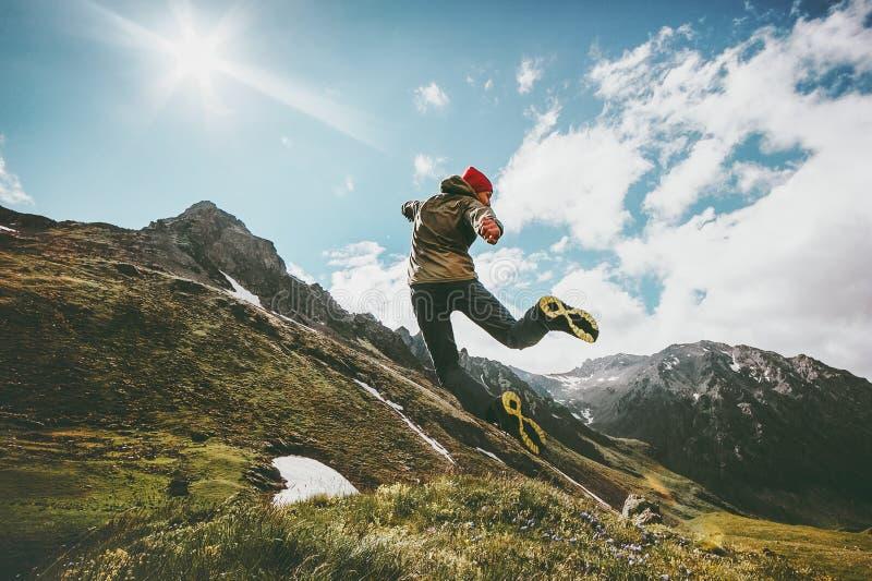 Framgångman som hoppar upp i berg arkivfoto