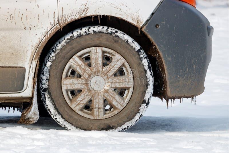 Framhjul av det smutsiga bilanseendet på snöslut upp royaltyfri fotografi