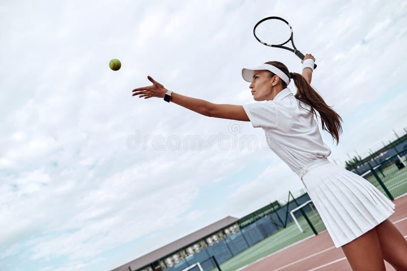 Framkalla din expertis Den attraktiva idrottskvinnan kastar bollen in i luften arkivfoto