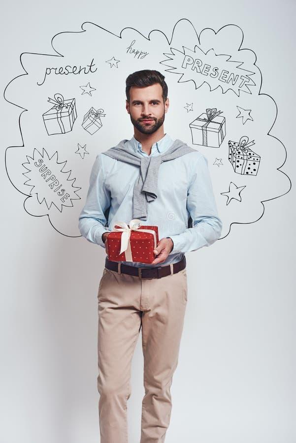 Framlägga för dig! Den eleganta mannen i tillfällig kläder rymmer en gåvaask och ler på kameran, medan stå mot grå färger arkivbild