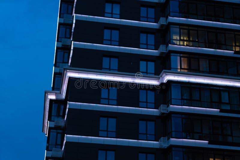 Frammenti di belle costruzioni moderne verso la fine della sera contro il cielo blu fotografia stock libera da diritti