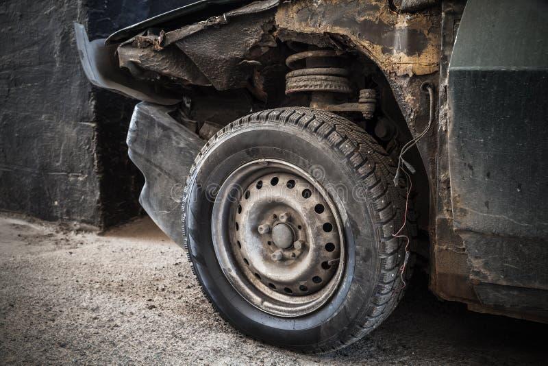 Frammento arrugginito abbandonato dell'automobile con la ruota immagine stock