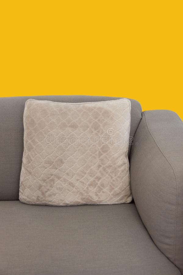 Frammento d'angolo dello strato ricoperto grigio beige con il cuscino decorativo del velluto sul fondo giallo della parete della  fotografie stock