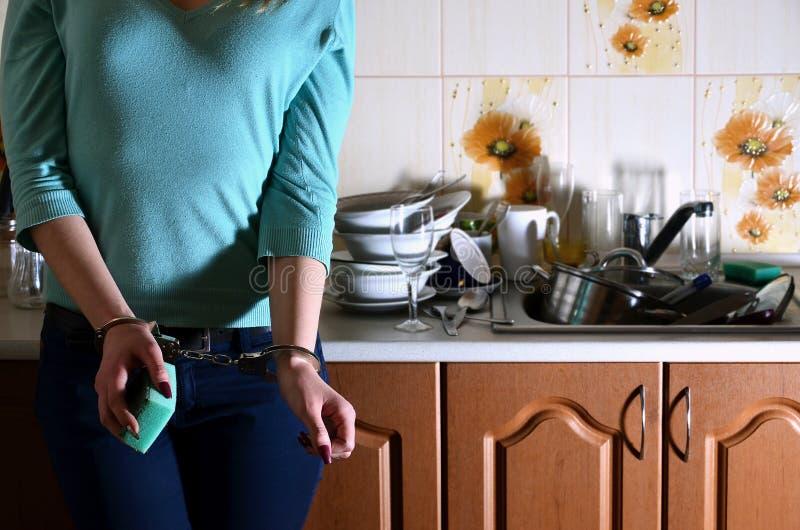 Frammento del corpo femminile ammanettato al contatore di cucina, f fotografie stock