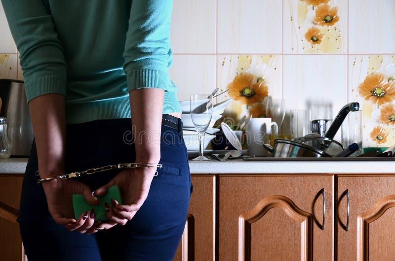 Frammento del corpo femminile ammanettato al contatore di cucina, f fotografia stock libera da diritti
