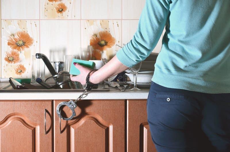 Frammento del corpo femminile, ammanettato al contatore di cucina fotografia stock libera da diritti