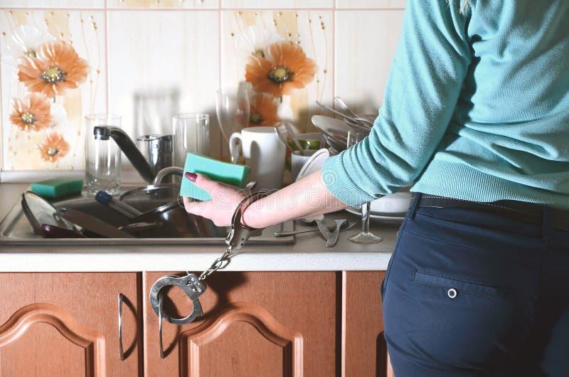Frammento del corpo femminile, ammanettato al contatore di cucina fotografie stock