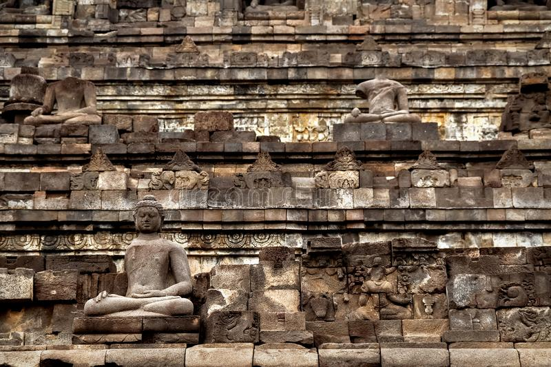 Frammento del tempio di Borobudur Statua di pietra antica di Buddha l'indonesia fotografie stock libere da diritti