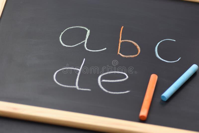 Frammento della lavagna nera con i gessi multicolori scritti mano di alfabeto latino Di nuovo ad alfabetizzazione della lettura d immagine stock