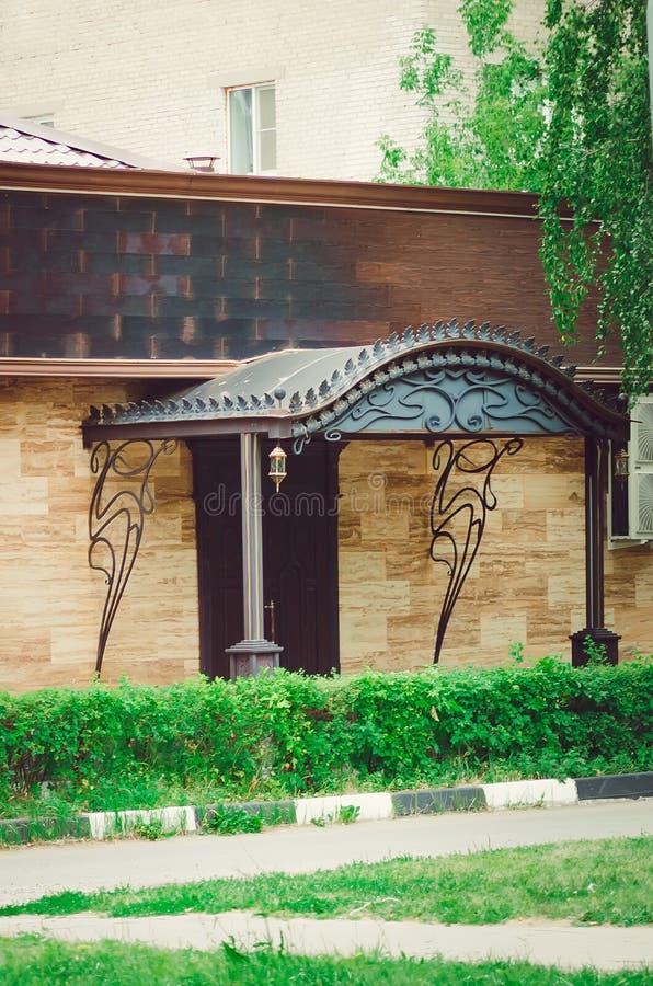 Frammento di bella casa ad un piano, un portico con un baldacchino del ferro fotografia stock
