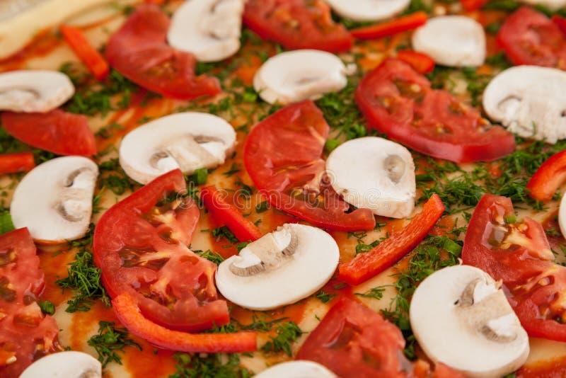Frammento di pizza crudo con pomodori e funghi, macrofano fotografie stock libere da diritti